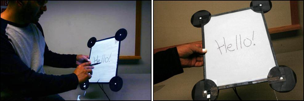 ▲ 一个手持剪贴板四角安装有光电传感器可以实时在投影仪下进行实时定位定位信息可以传回电脑将投影仪显示内容根据剪贴板方位调整显示变形最终达到像手持一个平板电脑进行显示的效果